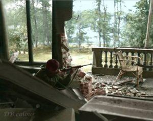 Squadron Sergeant Major Watt, HQ, B Squadron, 1st Wing, Glider Pilot Regiment, takes aim with an American M1 carbine from the first floor front balcony of the Hartenstein Hotel, Oosterbeek, near Arnhem in The Netherlands. Saturday, September 23, 1944