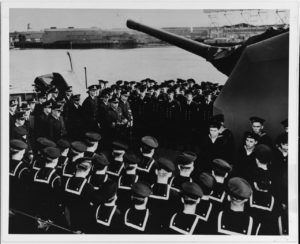 LCdr. Ernest E. Evans, USN, her Commanding Officer, is speaking in the left center. (Credits: U.S. Naval History and Heritage Command Photograph. NH 63368)