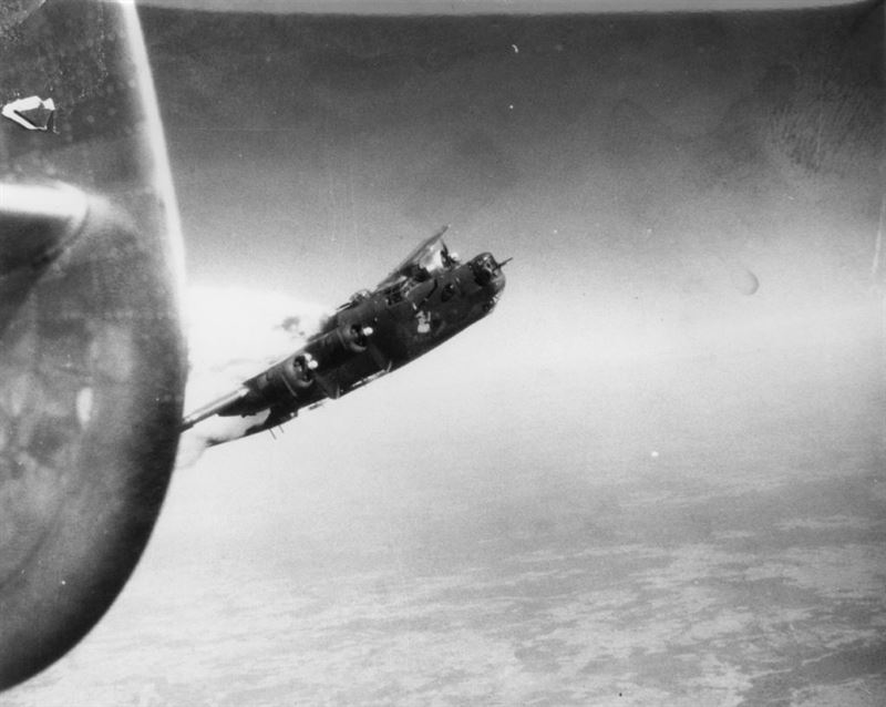 A B-24 Liberator (serial number 42-94812) nickname Little Warrior of the 493rd Bomb Group in flight with its engines aflame.